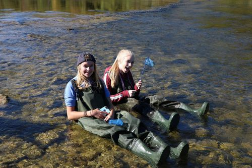 Students wearing hip waders sitting in the water sampling